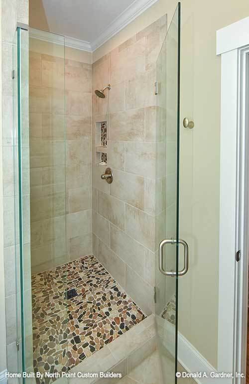 Walk-in shower with a glass hinged door marble tiled walls, pebble flooring, and chrome fixtures.