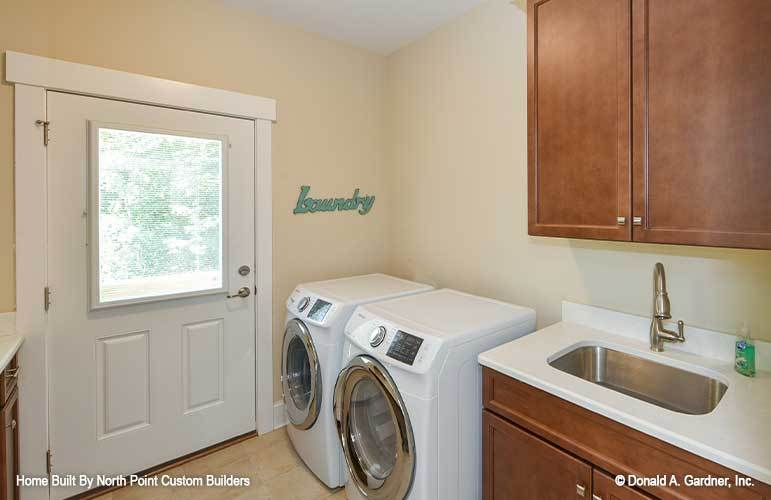 The utility room is filled with white front-load appliances, wooden cabinets, and an undermount sink.