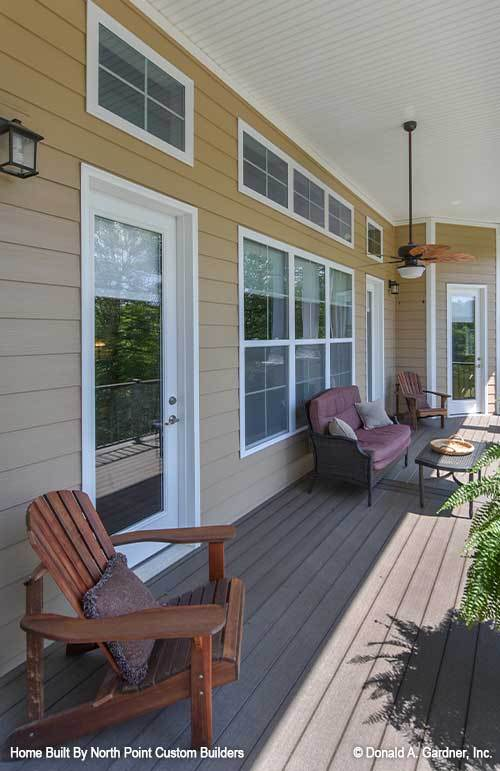 Rear porch with cushioned sofa and wooden loungers over wide plank flooring.