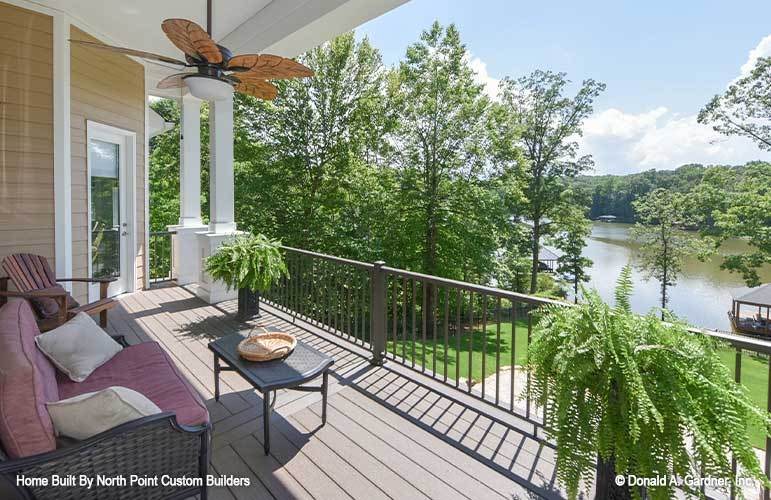 The covered porch overlooks a breathtaking lake view and lush greenery.