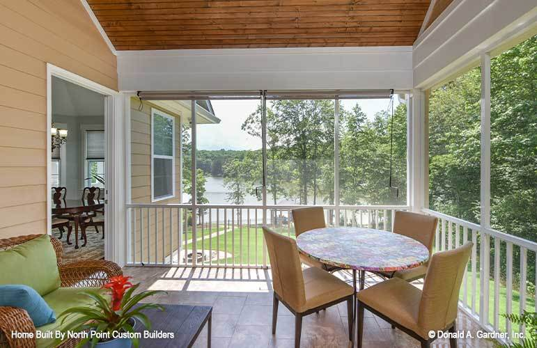 Screened porch with beige chairs, a round patterned table, and a wicker seat topped with green cushions and blue pillow.