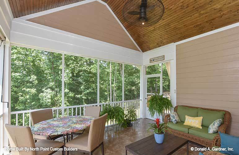 The screened porch has tiled flooring, brown shiplap walls, and a wood-paneled cathedral ceiling.