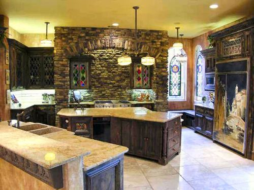 The kitchen has a stone cooking alcove, granite countertops, and an immense island.
