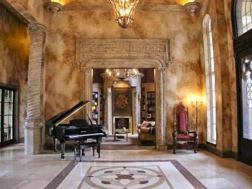 Foyer with a red baroque chair and a baby grand piano.