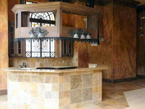 Wet bar with curved granite top counter clad in limestone tiles that match the flooring.