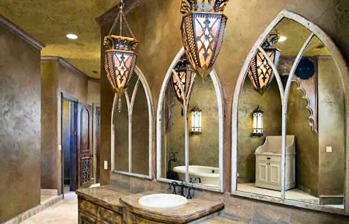 The primary bathroom offers a sink vanity, white washstand, and a freestanding tub reflected in the arched mirrors.