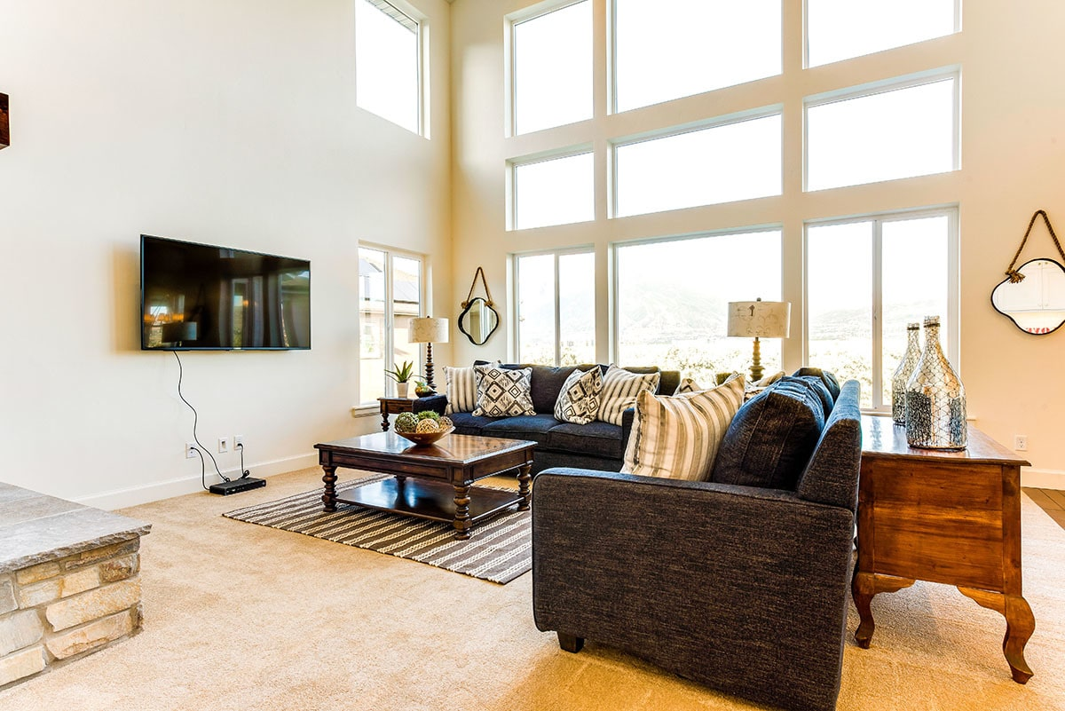 The living room has black sectionals, wooden tables, and a wall-mounted TV.