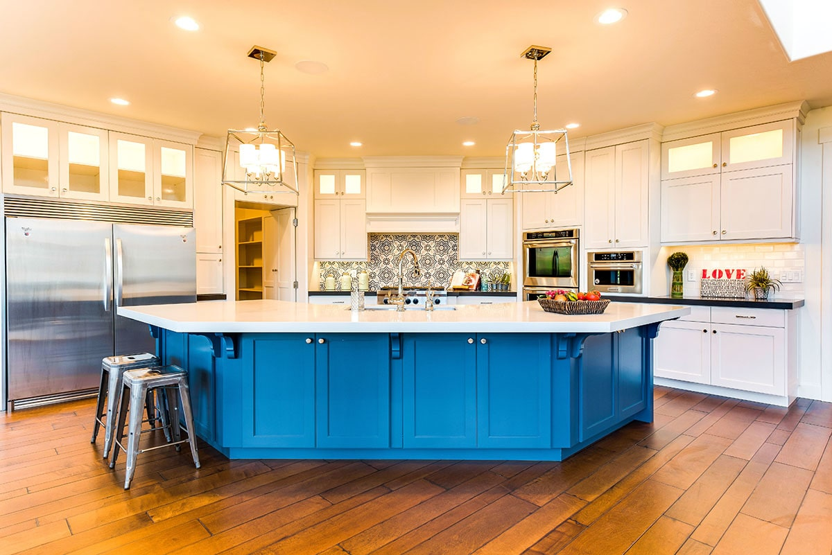The kitchen is equipped with stainless steel appliances, white cabinetry, quartz countertops, and a blue curved island.