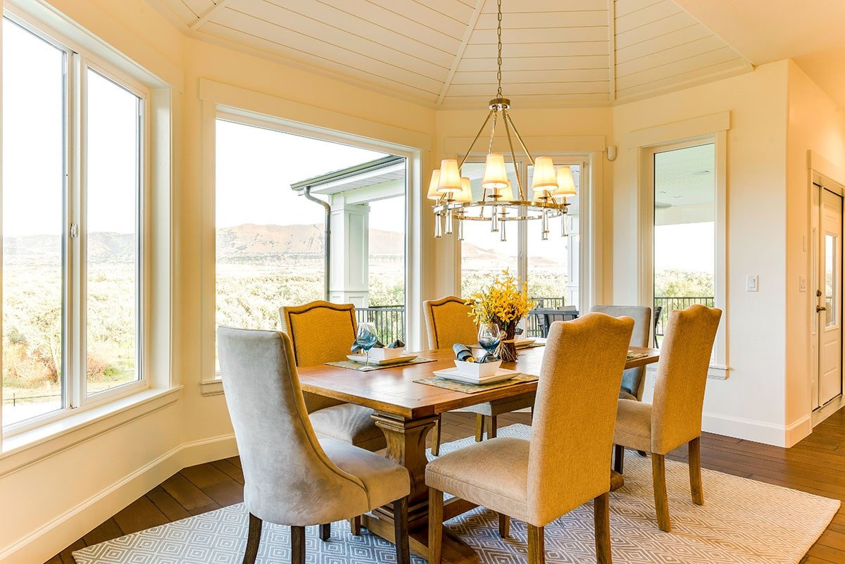 Bayed dining room with beige upholstered chairs and a rectangular wooden table well-lit by a round chandelier.