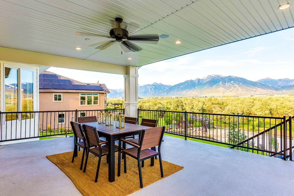 Covered porch overlooking the picturesque scenery. It has an outdoor dining set and a fan mounted on the paneled ceiling.