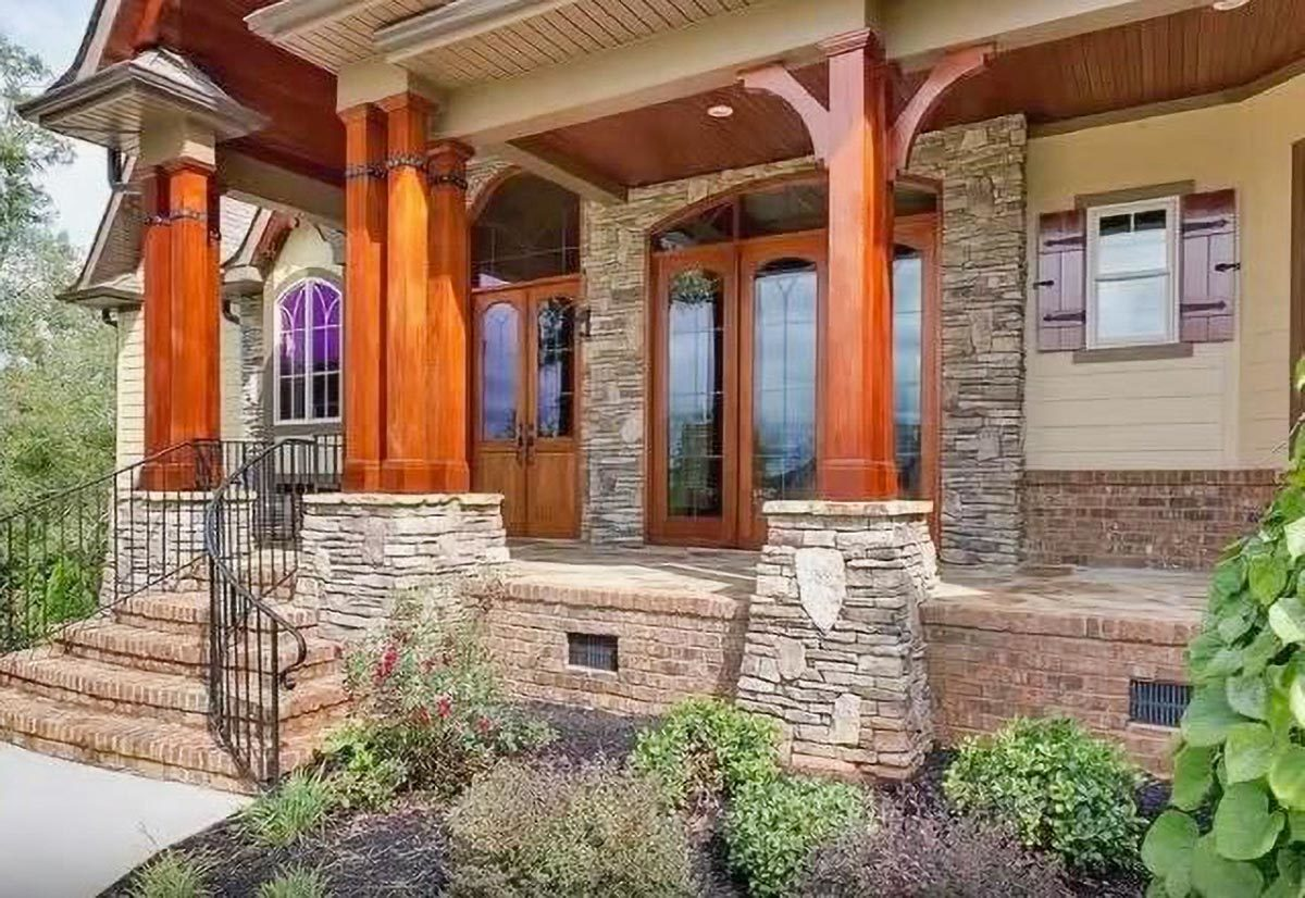 Covered front porch showing the wooden columns, glazed entry door, stone brick accents, and a stoop with iron railings.