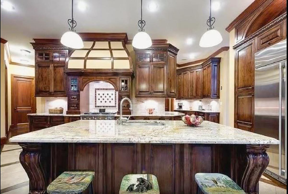The kitchen is equipped with stainless steel appliances, granite countertops, wooden cabinetry, and a breakfast island.