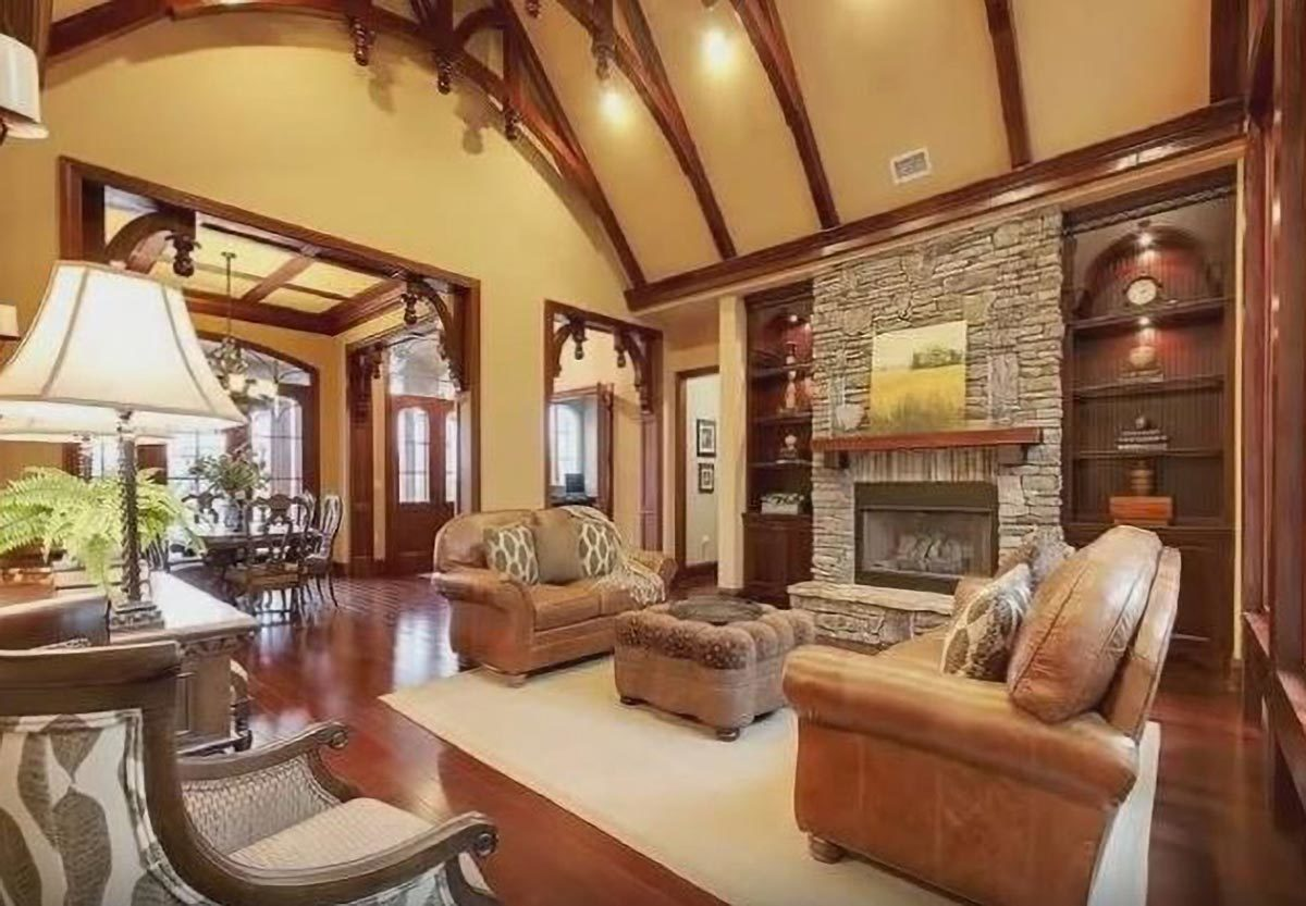 Living room with high beamed ceiling, leather couches, tufted ottoman, and a stone fireplace flanked by wooden built-ins.Living room with high beamed ceiling, leather couches, tufted ottoman, and a stone fireplace flanked by wooden built-ins.