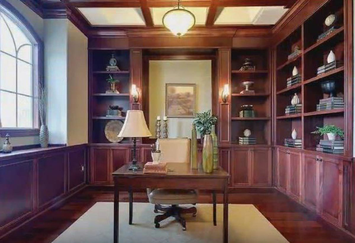 Study with a wooden desk, leather swivel chair, coffered ceiling, and built-in bookcases that blend in with the hardwood flooring.