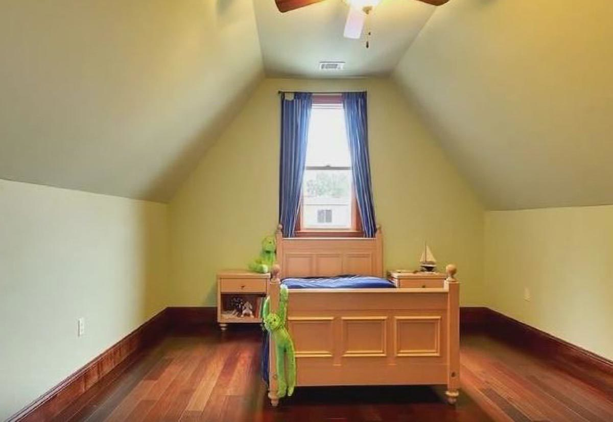 This bedroom has a vaulted ceiling, wooden furnishings, and bright yellow walls.