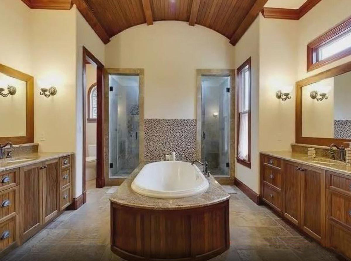 The primary bathroom has two vanities, a toilet room, a deep soaking tub, and a spacious walk-in shower with two glass doors.