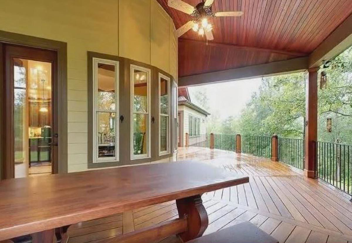 Covered porch with wide plank flooring, wrought iron railings, wooden table, and a ceiling fan mounted on the wood-paneled ceiling.