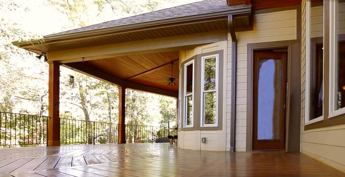 The covered porch transitions to an open deck with hardwood flooring arranged in a chevron pattern.