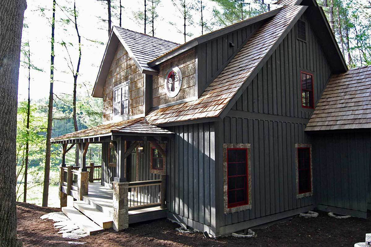 Right exterior view showing the vertical siding, red-framed windows, and a covered porch.