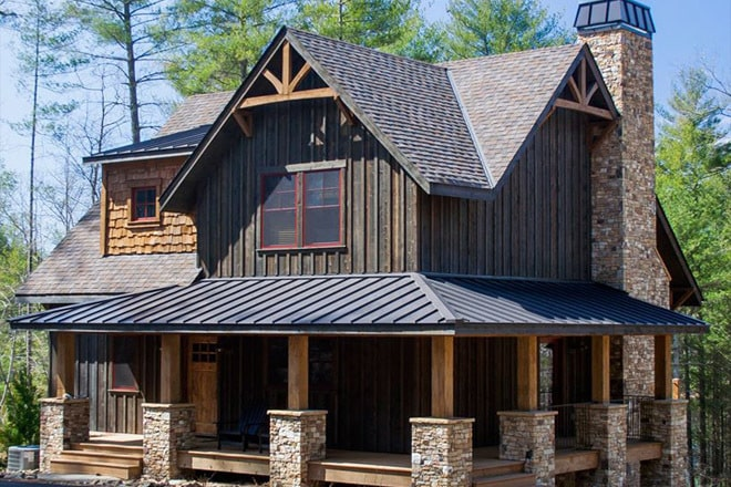 Left exterior view with a wrap-around porch, stone brick chimney, and gable roofs adorned by decorative wooden trims.