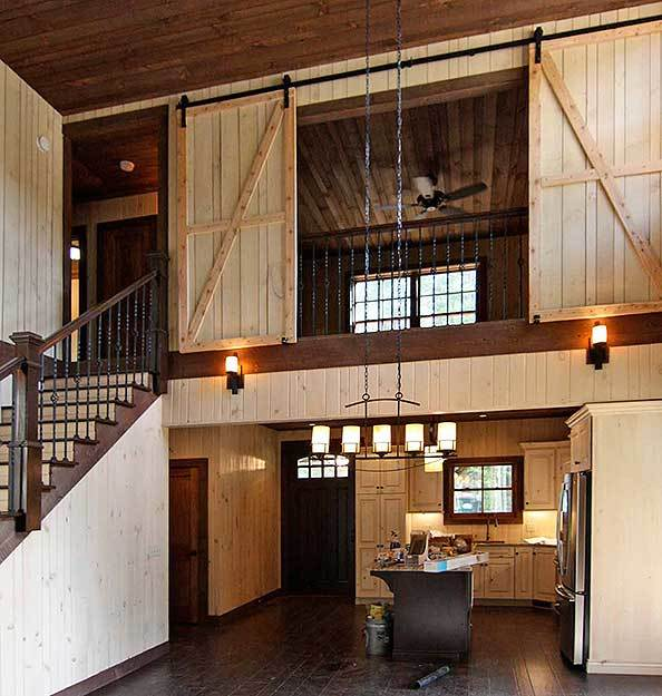 The open kitchen is situated under the second-floor bedroom that's enclosed in a sliding barn door.