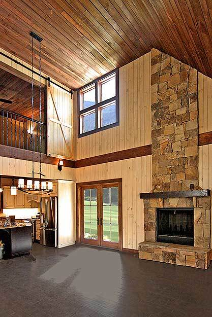 Living room with a towering wood-paneled ceiling, wide plank flooring, and a stone fireplace.