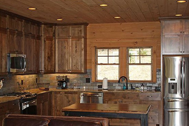 The kitchen is equipped with stainless steel appliances, granite countertops, wooden cabinets, and a center island.