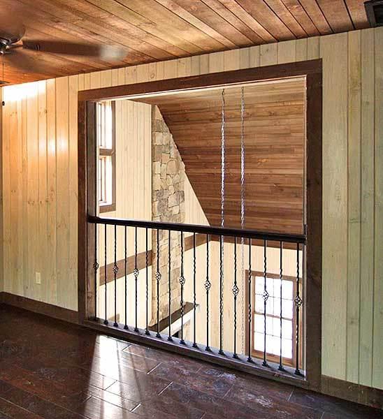 This bedroom has wrought iron railings overlooking the living room below.