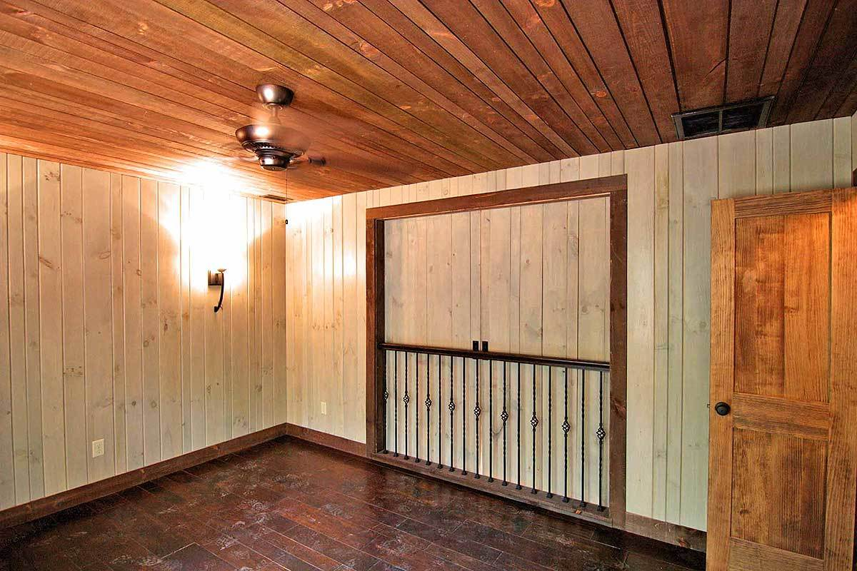 A farther view of the bedroom with closed doors, hardwood flooring, and wood-paneled walls and ceiling.