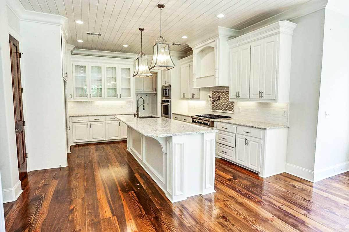 The kitchen is equipped with granite countertops, stainless steel appliances, white cabinets, and a center island.