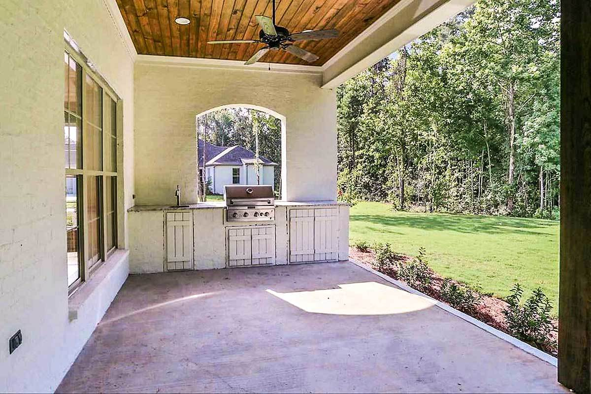 The rear porch has a summer kitchen complete with a small sink, rustic cabinets, and a built-in grill.