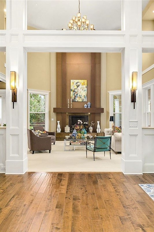 View of the living room from the foyer showing its surrounding white paneled half walls and trims.