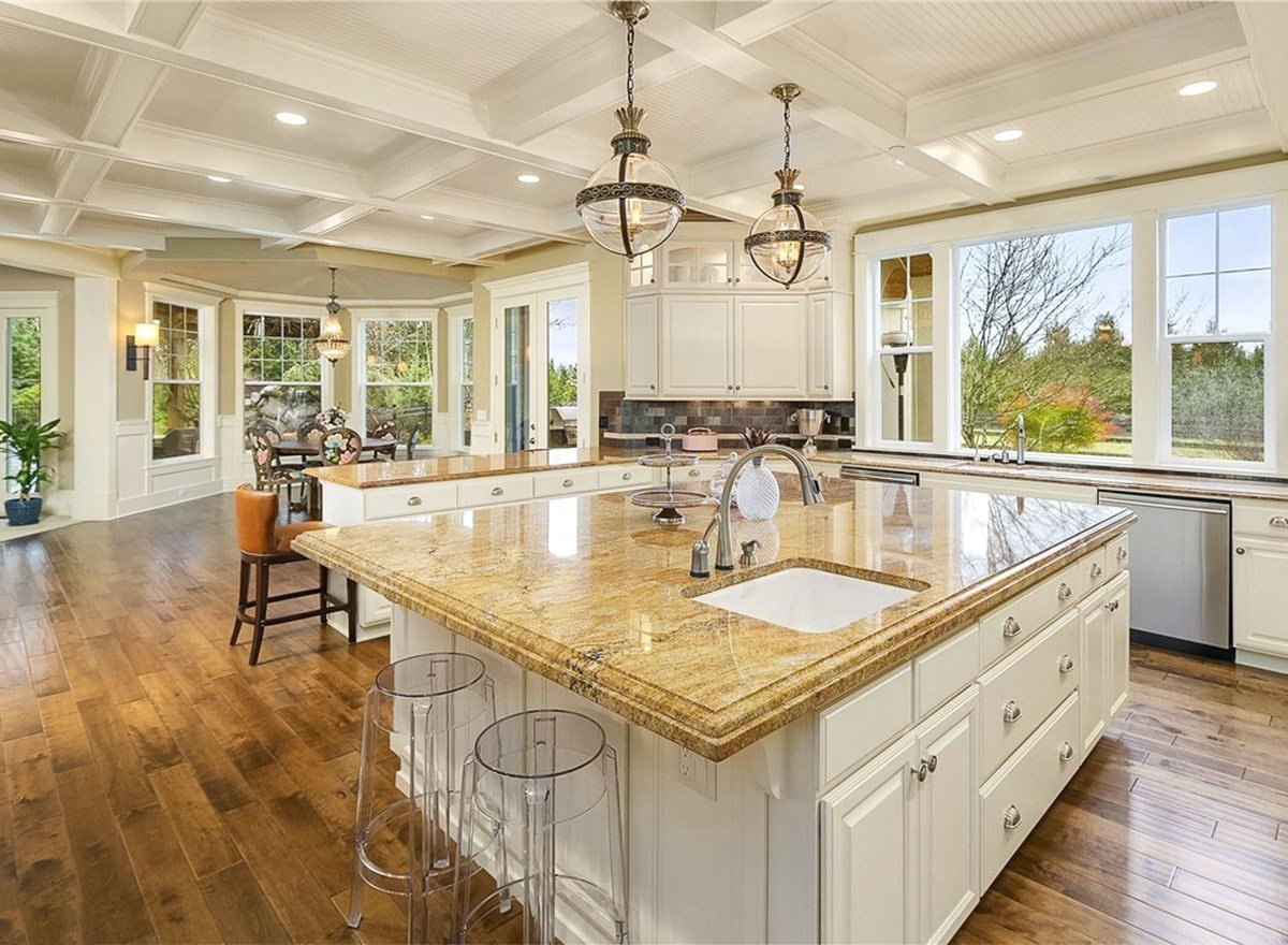 The kitchen is equipped with granite countertops, white cabinets, and an undermount sink fitted on the large center island.