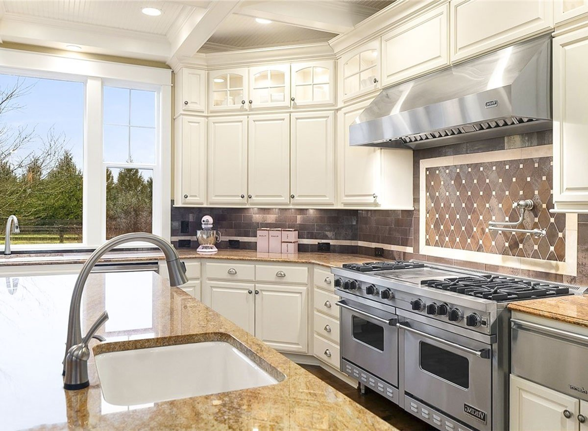Decorative tile backsplash accentuated the double oven range that's paired with a matching vent hood.