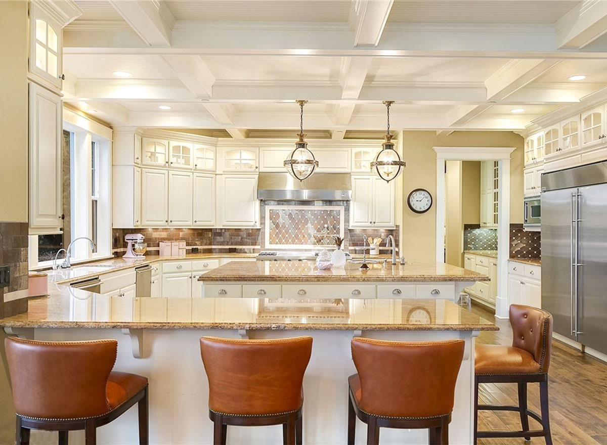 A farther view of the kitchen shows the white coffered ceiling and granite top peninsula lined with leather counter chairs.
