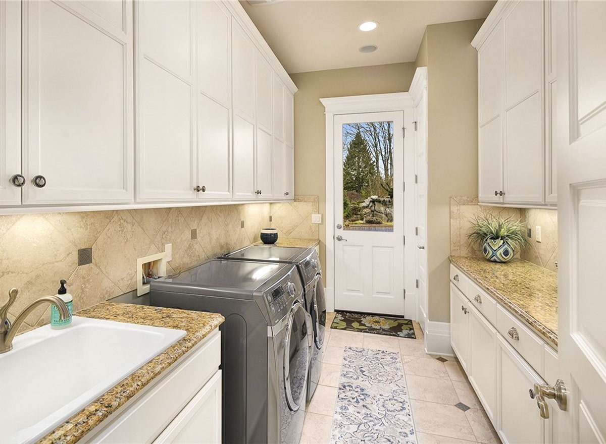 Utility with white cabinets, slate front-load appliances, and a porcelain sink.