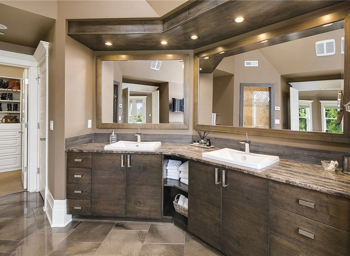The primary bathroom features a dual sink vanity with wooden cabinets and large mirrors.