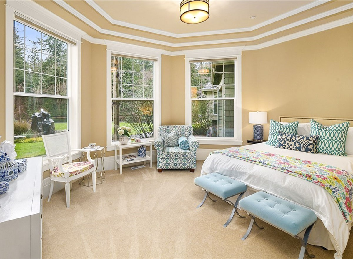 This bedroom has patterned seats, a white dresser, and a skirted bed with blue footstools at its end.