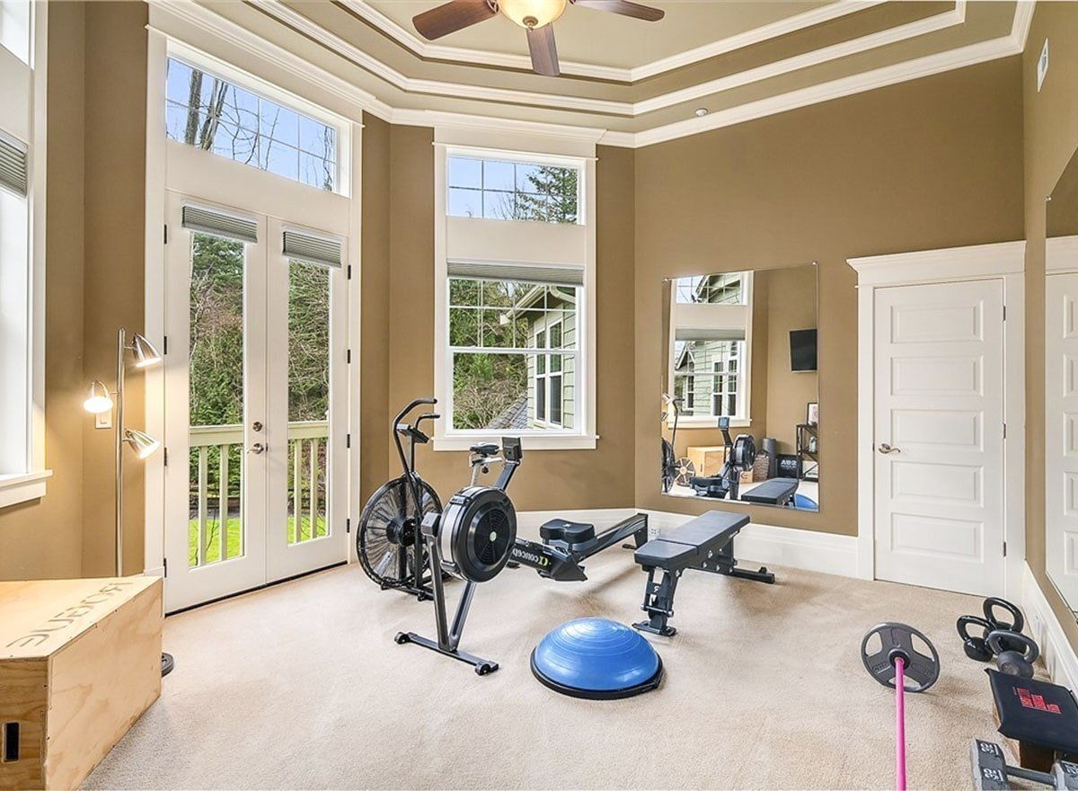 Home gym with carpet flooring, step ceiling, and a french door that opens out to the balcony.