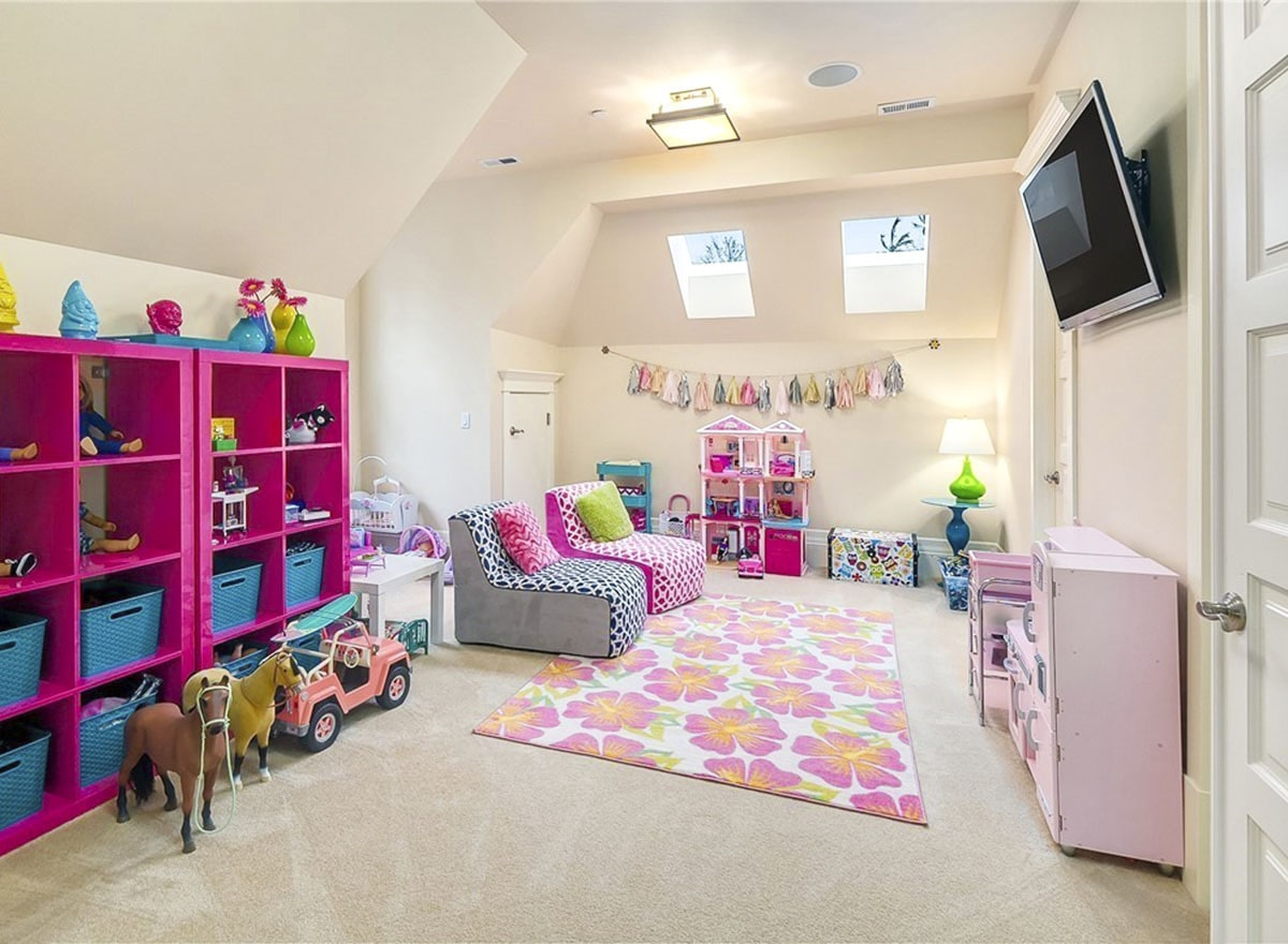 Kids' playroom with pink shelvings, patterned seats, a floral area rug, and a wall-mounted TV.