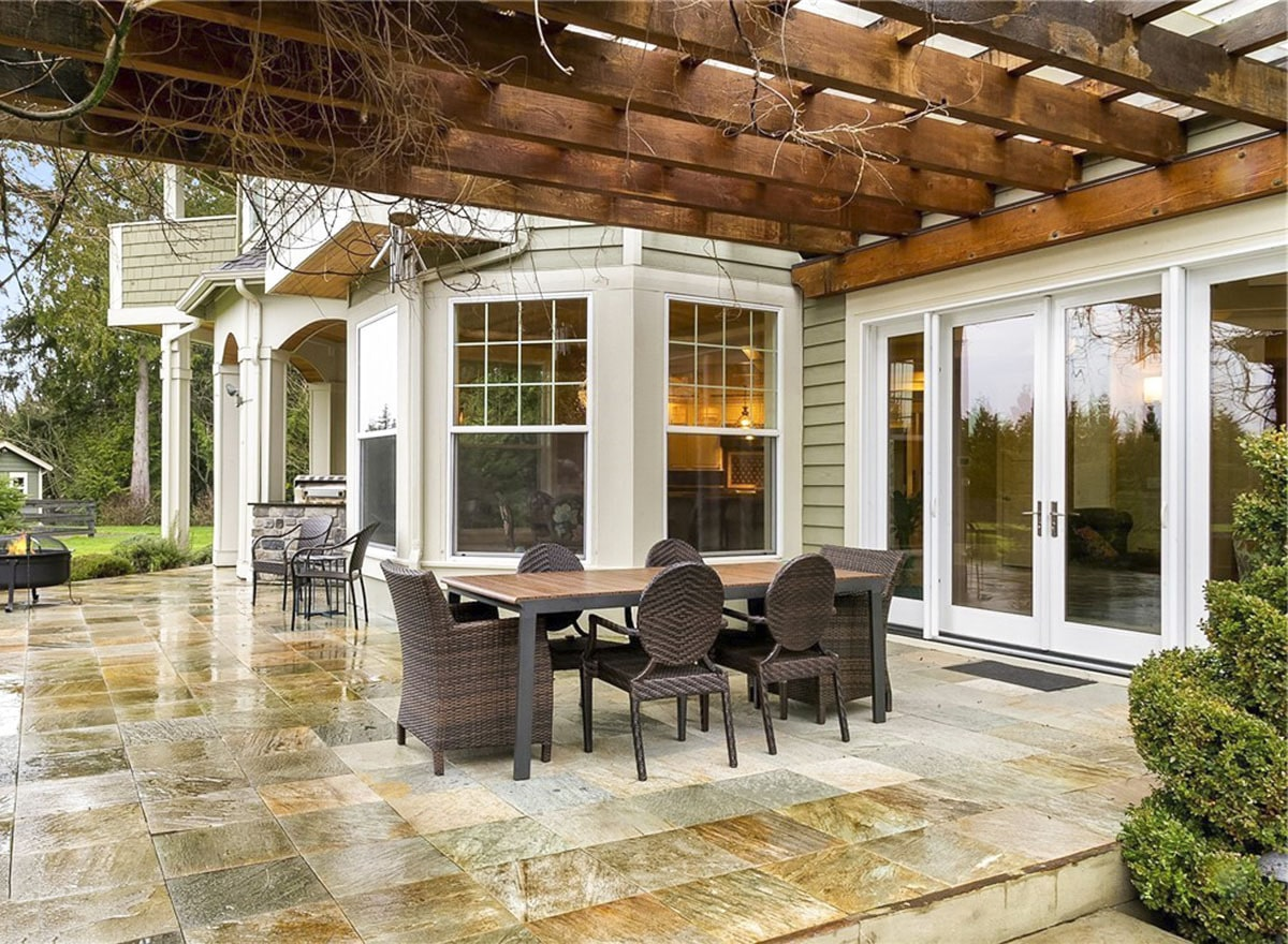 Rear patio with an outdoor dining set and a trellis roof.