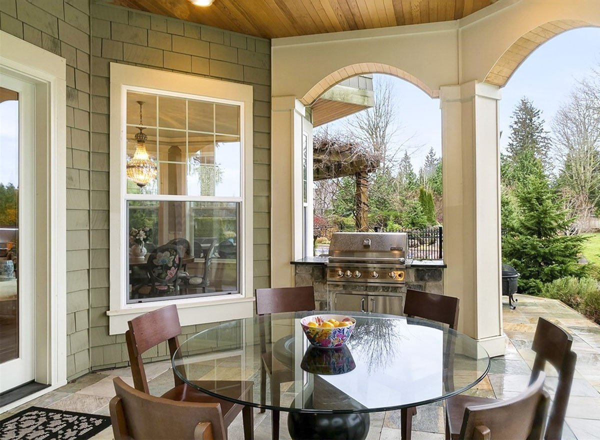 Covered patio with a summer kitchen, wooden chairs, and a glass top dining table.