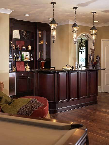 Wet bar with dark wood cabinets, black granite countertops, and glass pendants.