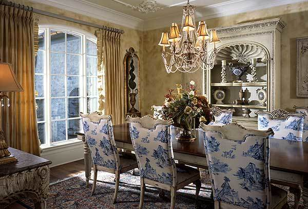The formal dining room has a white display cabinet, patterned chairs, and a rectangular table well-lit by a beaded chandelier.