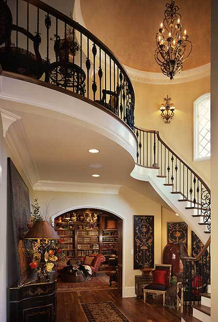 Foyer with classy seats, intricate winding staircase, and a soaring ceiling.
