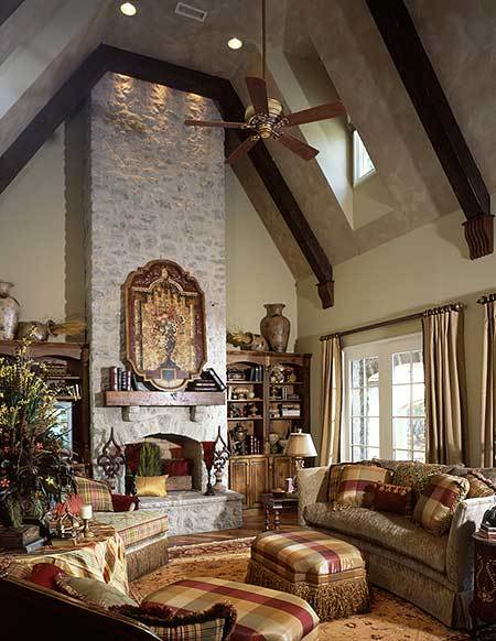 The family room has a stone fireplace, checkered seats, and a vaulted ceiling with exposed beams.