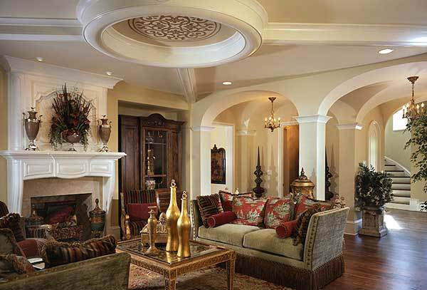 Living room with skirted sofas, marble fireplace, and a decorative tray ceiling.