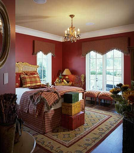 The guest room has red walls, a carved wood bed, and checkered stools sitting next to the white-framed windows.