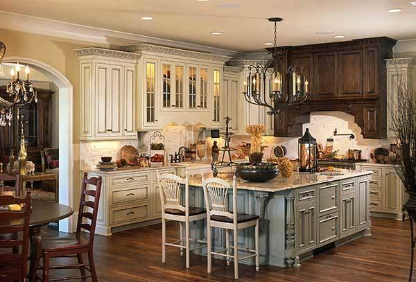 The kitchen offers white and wooden cabinets, a candle chandelier, and a large center island.