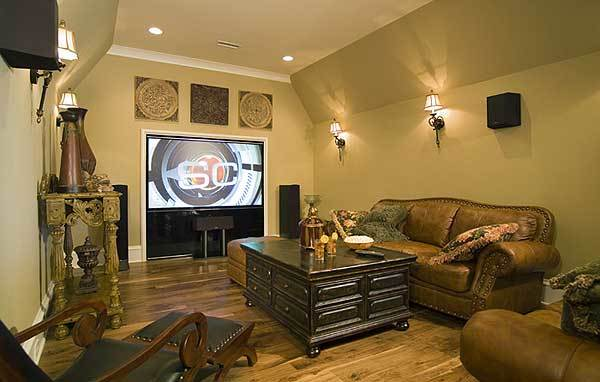 Media room with brown leather sofas, wooden lounger, dark wood coffee table, and a flatscreen TV.